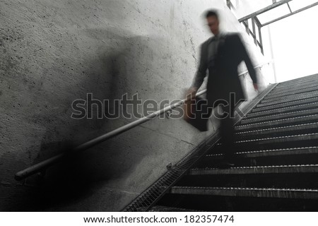 Busy Businessman Rushing Down the Stairs. Motion blur to show the speed and room for your text. - stock photo