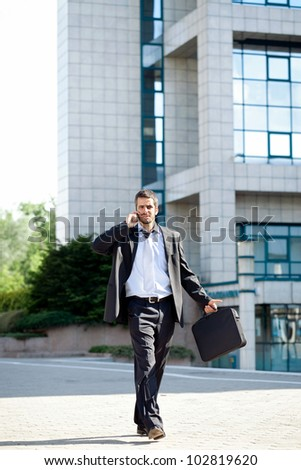 Busy businessman talking on mobile phone while walking - stock photo