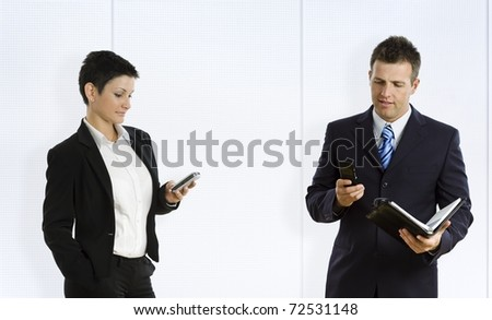 Busy businesspeople using mobile phone and personal organizer.? - stock photo