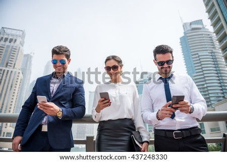 Busy businesspeople using mobile phones outdoors. - stock photo