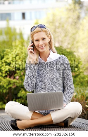 Busy businesswoman sitting at outdoor with laptop and making call. Attractive professional working at coffee break.