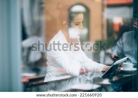 Busy businesswoman talking on phone and using tablet computer in cafe - stock photo