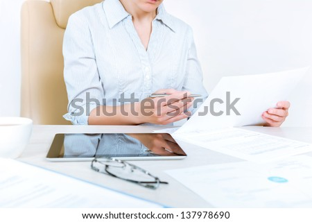 Busy caucasian businesswoman wearing in casual shirt sitting at desk and check documents in the office