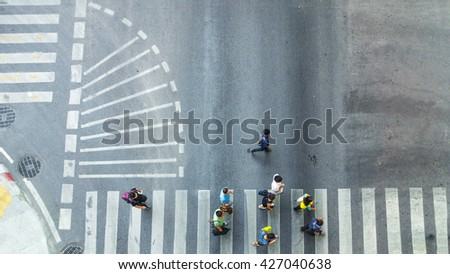 Busy city crowd move to pedestrian crosswalk on traffic road (Aerial photo, top view) - stock photo