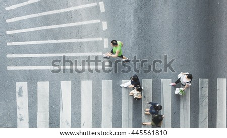 Busy city people are walking to pedestrian crossing on traffic road (Aerial photo, top view) - stock photo