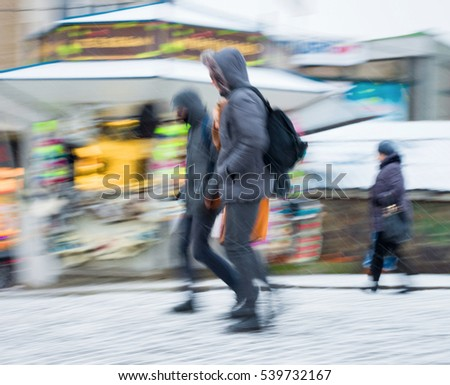 Busy city people going along the street in winter snowy day. Intentional motion blur