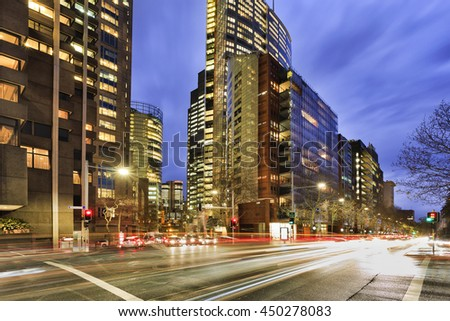 Busy city streets traffic in Sydney at intersection of Elizabeth street with illuminated office buildings at rush hour during sunset.