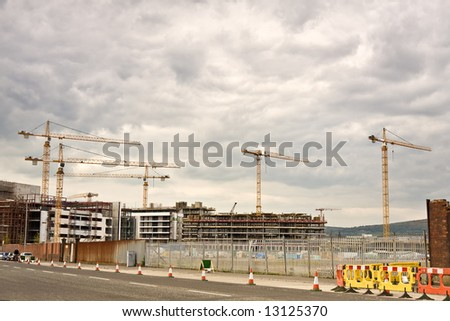 busy construction site with cranes seen from afar - stock photo