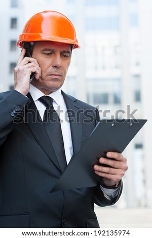 Busy contractor. Confident mature man in formal wear and hardhat talking on the mobile phone and looking at clipboard while standing outdoors - stock photo