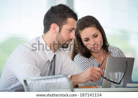 Busy couple of managers working with laptop in office