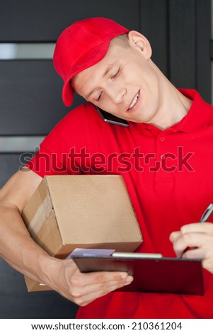 Busy courier calling on mobile phone and writing on clipboard - stock photo