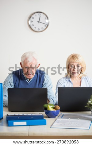 Busy elderly businesspeople working on laptops - stock photo