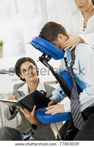 Busy executive working in massage chair, while getting back massage in office.? - stock photo