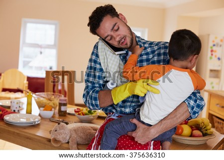 Busy Father Looking After Son Whilst Doing Household Chores - stock photo
