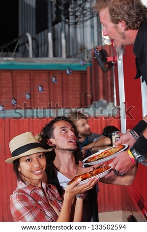 Busy food truck owner with happy customers - stock photo