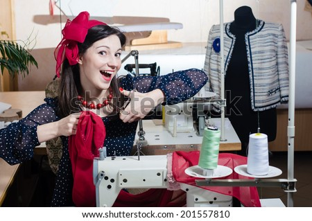 Busy funny working tailor: beautiful young pin up girl having fun posing with scissors & sewing machine happy smiling looking at camera on busy workshop studio background portrait image - stock photo