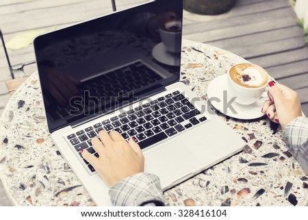 Busy girl with laptop and cappuccino