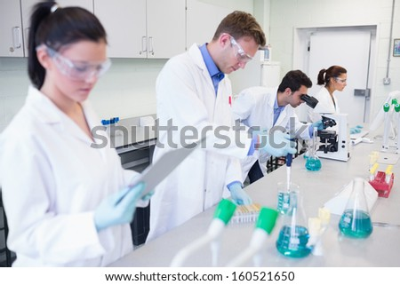 Busy group of researchers carrying out experiments in the laboratory - stock photo