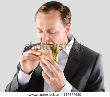 Busy hardworking business man eats lunch at his desk while working - stock photo
