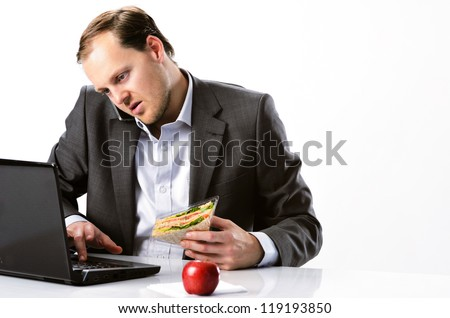 Busy hardworking businessman multitasking, talking on mobile cell phone typing on laptop computer and having healthy sandwich lunch with red apple - stock photo
