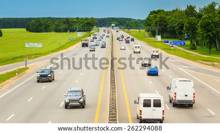 Busy Highway During Day. Heavy Traffic Moving At Speed On Motorway. Number Plates And Car Logos Removed - stock photo