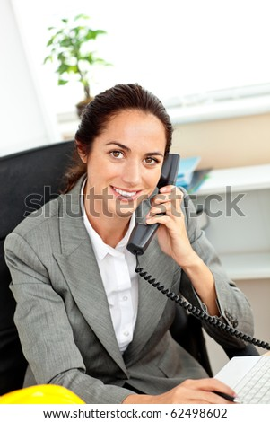 Busy hispanic female architect using her laptop while talking on phone in her office - stock photo