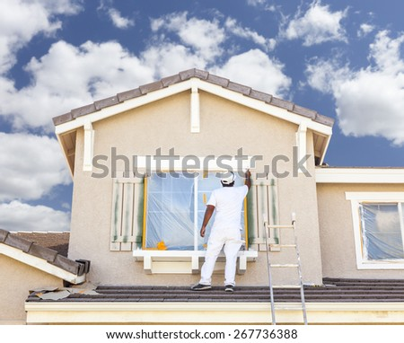 Busy House Painter Painting the Trim And Shutters of A Home. - stock photo