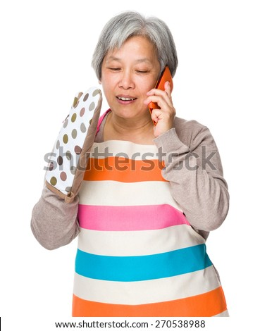 Busy housewife talk to mobile phone - stock photo