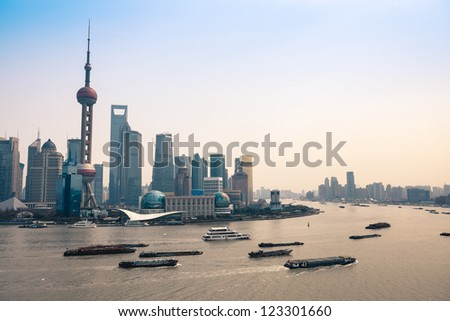 busy huangpu river at dusk with shanghai skyline - stock photo