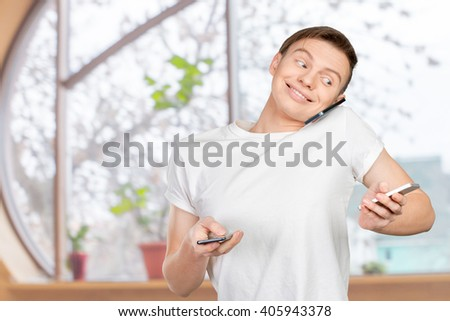 Busy man talking several phones same time - stock photo