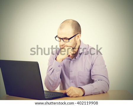 Busy man with beard in glasses thinking over laptop with  on the table. Isolated on gray background