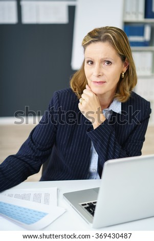 Busy middle-aged businesswoman with a distracted expression pausing while reading documents at her desk to look at the camera