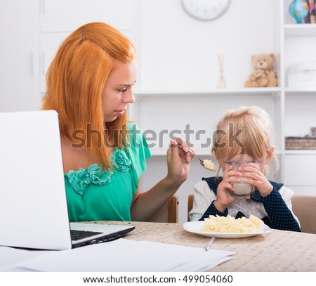 busy mom working on computer and giving porridge to small girl indoors