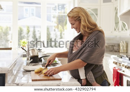 Busy Mother With Baby In Sling Multitasking At Home - stock photo