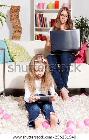 Busy mother working while child is playing - stock photo