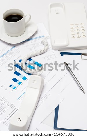 Busy office desk telephone on paper charts business meeting