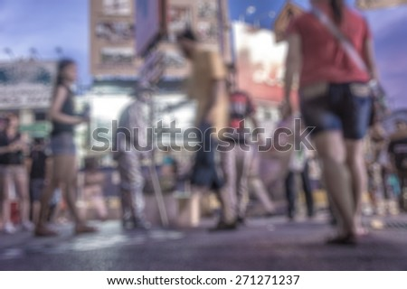 Busy people on street at night in defocused blur concept vintage color style.