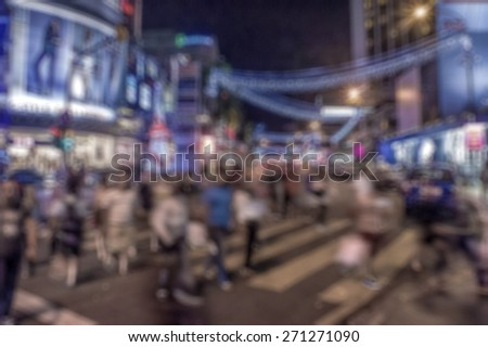 Busy people on street at night in defocused blur concept with vintage color style. - stock photo