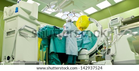 Busy surgery room in hospital, doctors in medical uniforms operating on patient - stock photo