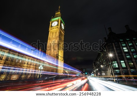 Busy Traffic Intersection at night with streaking car lights at the Houses of Parliament and Big Ben in London, England, United Kingdom - stock photo