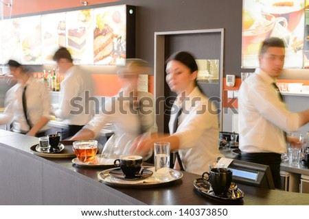 Busy waiter and waitresses working at bar night - stock photo