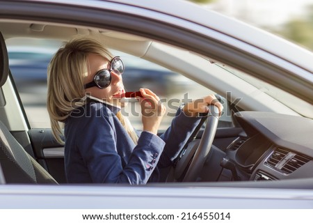 Busy woman manage to talk on phone and do makeup while driving a car - stock photo