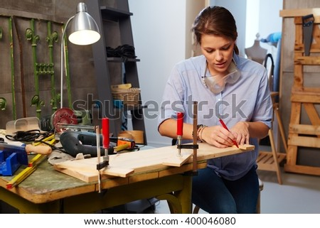 Busy woman tinkering in workshop. - stock photo