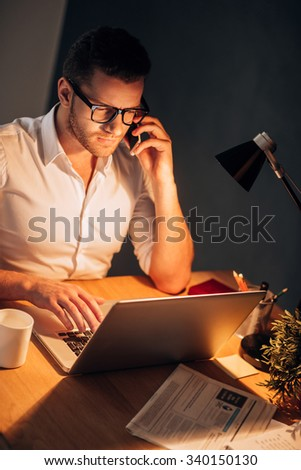 Busy working even at night. Top view of confident young man in eyewear talking on the mobile phone and working on his laptop while sitting at his working place at night time - stock photo