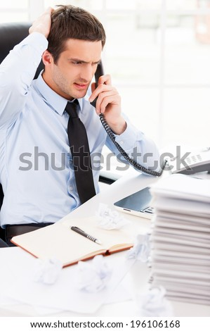 Busy working in office. Worried young man in formalwear talking on the telephone and holding hand in hair while sitting at his working place - stock photo