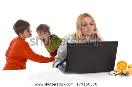 busy, working mother with computer while her kids fighting at background - stock photo