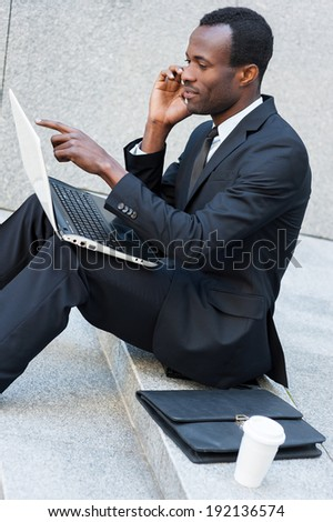 Busy working outdoors. Side view of confident young African man in formalwear talking on the mobile phone and working on laptop while sitting outdoors - stock photo
