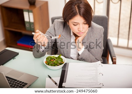 Busy young business woman eating a healthy lunch while working in her office - stock photo