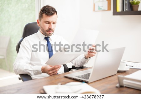 Busy young businessman with a beard reviewing some performance charts in his office