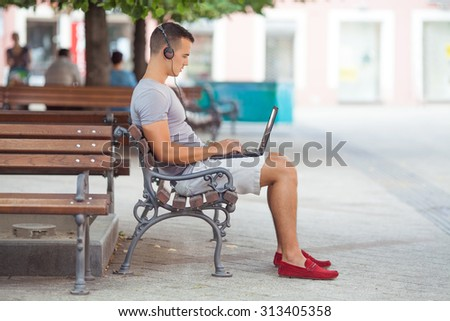 Busy young businessman working on his laptop while sitting on the park bench - stock photo